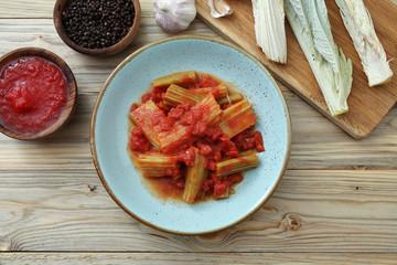 cardoni in salsa di pomodoro su tavolo di cucina