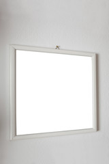 empty frame hange on a white wall with clipping path included and copy space