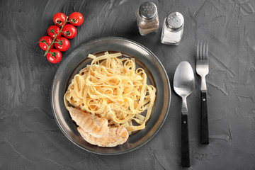 Plate of delicious pasta with cheese and grilled chicken fillet on table, top view