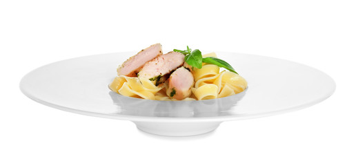 Plate of delicious pasta with chicken fillet on white background