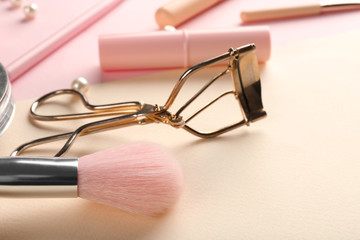 Brush for applying makeup and eyelash curler on color background, closeup Wall mural