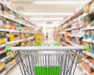Empty shopping cart with supermarket shelves aisle interior blur defocused background