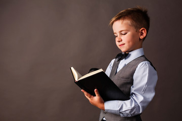 Smart little boy with a loupe poses in a suit in the studio and reads a book