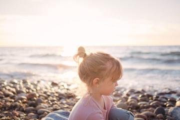 Kleines Mädchen bei Sonnenuntergang am Strand