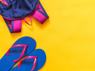 Travel vacation background. Flip flops, backpack, on a yellow background. Flat lay