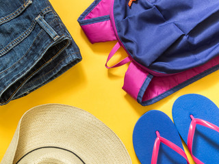 Travel vacation background. Flip flops, backpack, jeans, hat on a yellow background. Flat lay