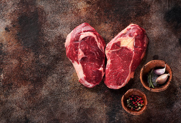 Wall Mural - Two raw ribeye steaks on a cutting board with spices. Top view