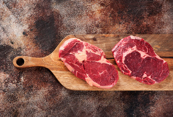 Wall Mural - Two raw ribeye steaks on a cutting board. Top view