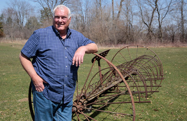 Michigan resident Jerry Smith poses for a picture on his family farm next to a 'dump rake' once used by his grandfather, as he talks about voting and the U.S. presidential election, in Dexter, Michigan