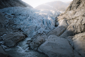 Two hikers walking towards a blue glacier with river in Norway
