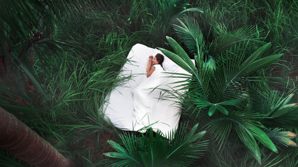 A hidden place. Sleeping woman in deep jungle forest lies on airbed,View from above