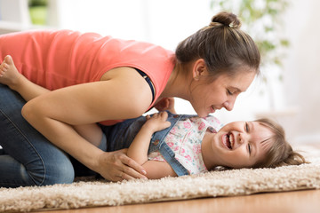 Family - mom and kid daughter having a fun on floor at home. Woman and child relaxing together.