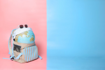 Travelling globe going on vacation in backpack with sunglasses and  bandana on soft pink and light blue pastel colored background, Copy space, Trendy vanilla colors