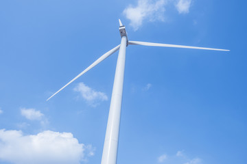 White wind turbine on blue sky with white clouds.
