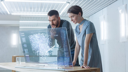 In the Near Future Male and Female Computer Engineers Talk While Working on the Transparent Display Computer. Screen Shows Interactive Neural Network Project, Futuristic User Interface.