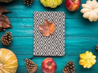 Notebook on green autumn background with pumpkin, apples, yellow leaves. Fall still life flat lay.