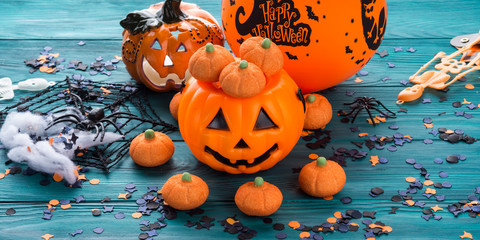 Halloween trick or treat still life on dark green. Toy pumpkin, sweets, marshmalllow, confetti. Holiday mood background