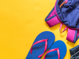 Travel vacation background. Flip flops, backpack, jeans on a yellow background. Flat lay