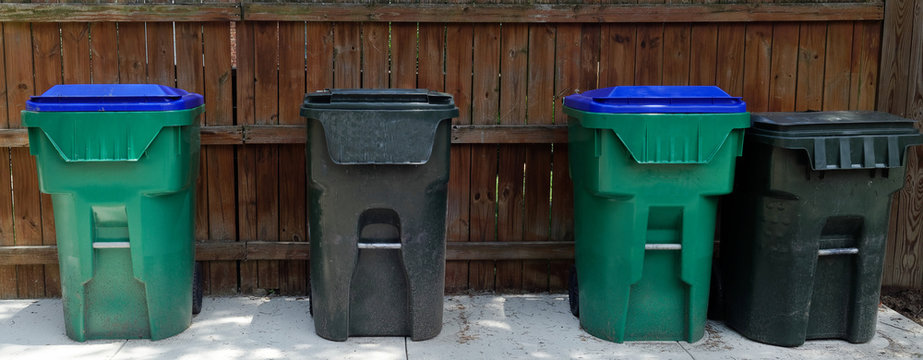 Large plastic trashcans standing in front of fence in residential alley.