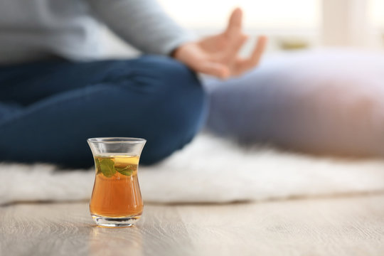Cup of hot tea and woman meditating on floor at home