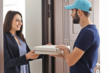 Young woman receiving cardboard pizza boxes from delivery man
