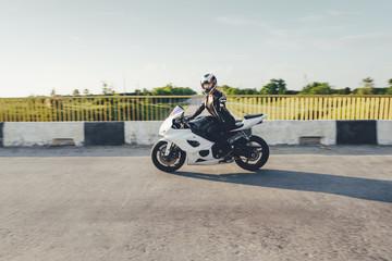 Woman biker driving a motorbike on a road