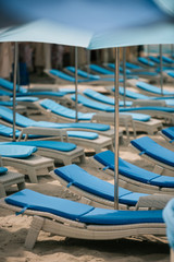 empty chaise lounges and umbrellas at beach