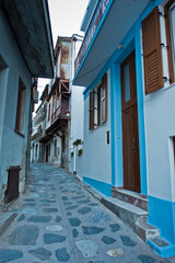 Foto auf AluDibond Gezeichnet Straßenkaffee Narrow, winding and steep cobblestone streets at sunset, city of Skopelos, Skopelos island in Greece