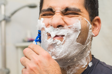 man shaves his beard with a razor