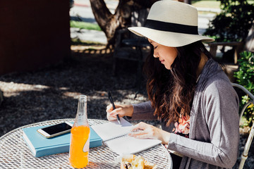 Young woman sitting outdoors, writing in notebook