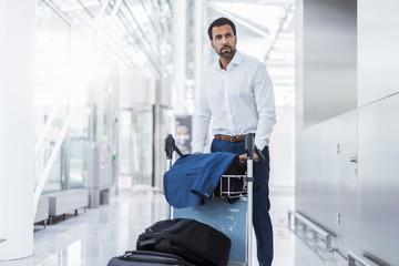 Businessman using baggage cart
