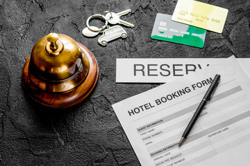 booking form for hotel room reservation, pen and ring dark backg