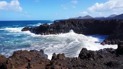 Los Hervideros rocky coast with wavy ocean and volcanos on the background, Lanzarote, Canary Islands, Spain