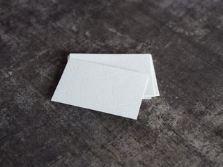 Stack of blank white textured business cards on a wooden surface