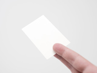 Blank white business card held by two fingers, isolated, mock up
