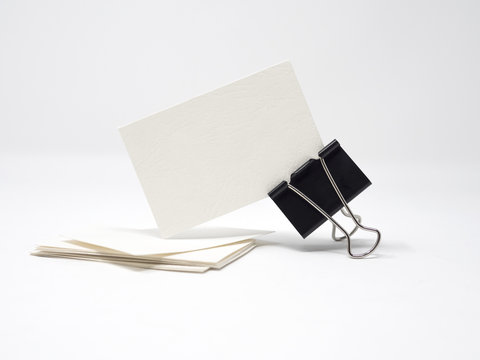 White blank business card being held by a black binder clip, isolated, mock up