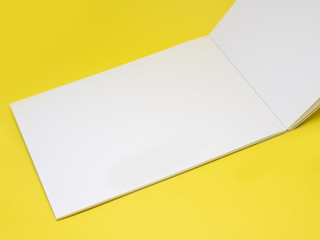 Vertically open blank notepad on a yellow background, close up