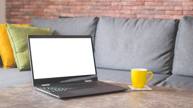 White screen laptop and a yellow cup on a table by a couch mock up