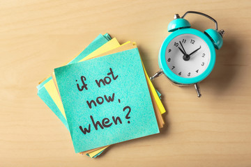 """Sticker with phrase """"If not now, when?"""" and alarm clock on table. Time management concept"""