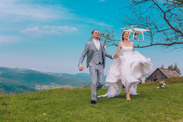 Young coulple running to flying drone. Concept of aerial shooting. White drone flying aroud bride and groom. Advertising picture.