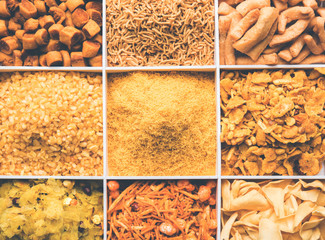 Indian Tea-time snacks like sev, chivda, farsan, mixture, boondi, bakarwadi etc served in white wooden box with cells. selective focus