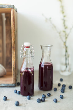 Close-up of juice in bottles with blueberries on table