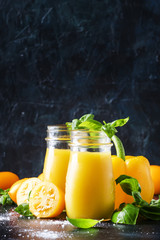 Useful and healthy smoothie or juice from yellow tomatoes and bell peppers with green basil in glass bottles, black background, selective focus