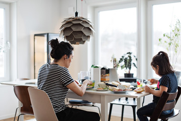 Mother and daughter having food at dining table