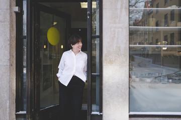 Smiling young female designer standing at doorway of studio