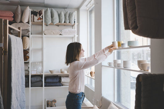 Woman arranging ceramics on shelf in store