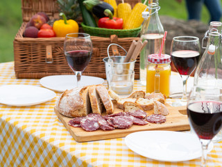 Party in the countryside. Table detail of a picnic decorated outdoors in summer with vegetables, red wine in glasses, Italian sausage, homemade bread on a wooden cutting board on checkered tablecloth