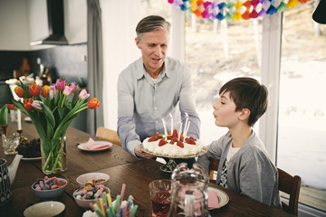 Boy blowing candles while grandfather holding birthday cake at table during party
