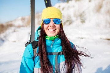 Portrait of sports girl with skis and sticks in winter