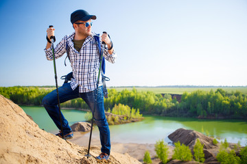 Picture of tourist man with backpack with sticks for walking on hill